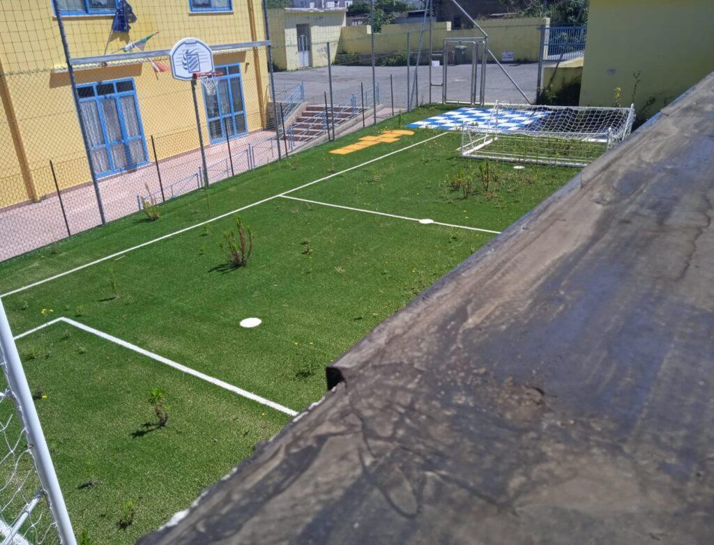 erbacce e piante selvatiche sul terreno di gioco del campetto realizzato all'esterno della scuola Rodari